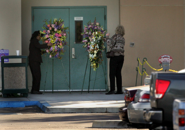 Wreaths and flowers have been placed at several of the employee entrances of the United States Postal Service distribution center in Goleta, Calif.