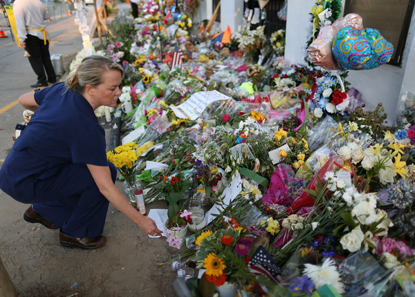 Jessica Oliver leaves flowers on a memorial in front of the Emanuel African Methodist Episcopal Church.
