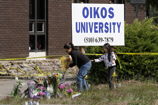 Maria Campomanes and her daughter Maelauni, 9, leave flowers for Oikos University victims outside of the school in Oakland, Calif., Wednesday, April 4, 2012.