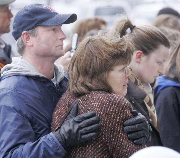 Terry Bradshaw, left, comforts his wife, Kim, center, and daughter Jamie, right, while they visit a memorial outside the Von Maur department store in Omaha, Neb., Saturday, Dec. 8, 2007.