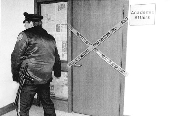 A University of Iowa campus security officer checks the hallway outside the sealed Office of Academic Affairs in Jessup Hall.