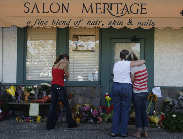 Mourners stop by to pay their respects at the door of Salon Meritage in Seal Beach on the morning after eight people were shot to death and a ninth wounded by suspected gunman Scott Dekraai October 13, 2011.