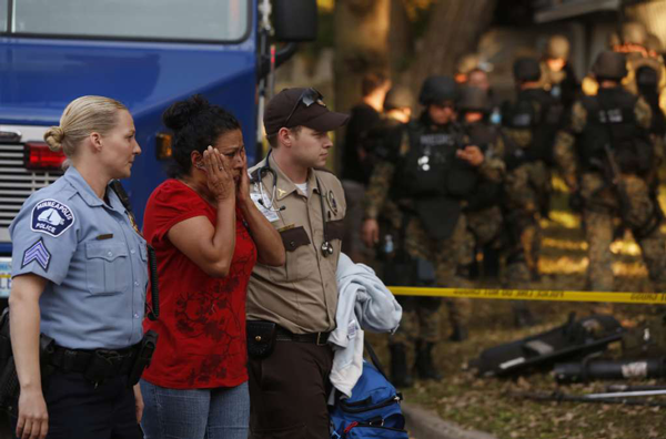 At a fatal shooting in the Bryn Mawr neighborhood of Minneapolis, Minnesota, people are moved to a safe area from the crime scene on Thursday, September 27, 2012.
