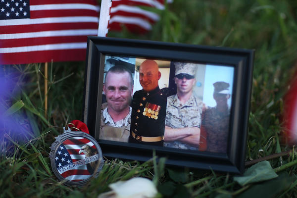 Photos of four slain Marines are placed at a makeshift memorial at a military recruiting center in Chattanooga