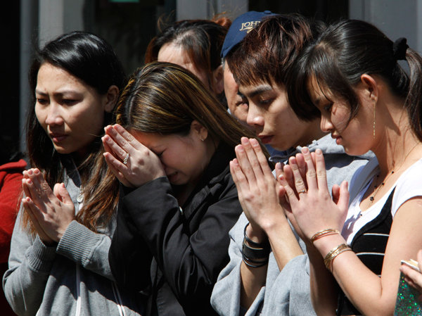 Mourners pray with relatives of shooting victims Lan Ho and Long Huynh outside the American Civic Association on Sunday, April 5, 2009, in Binghamton, New York