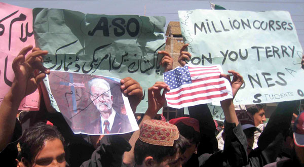 "A protester holds a picture of US pastor Terry Jones, during a rally against ""Innocence of Muslims"" in Chaman, Pakistan."