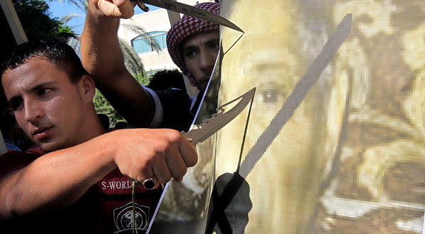 Palestinian muslims cut the poster of Morris Sadek, the Egyptian born Christian living in the US during a protest in front the UNSCO headquarters in Gaza City.