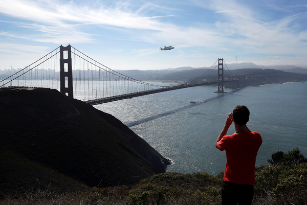 A spectator takes a photo of the Space Shuttle Endavour as it flies on top of a modified 747 jumbo jet over the Golden Gate Bridge while traveling to Los Angeles Friday in Sausalito.