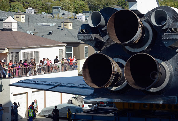 The space shuttle Endeavour squeezes through a neighborhood lined with apartment buildings as it is transported to the California Science Center on Saturday.