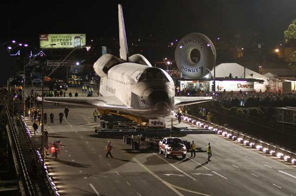 Space shuttle Endeavour is pulled along W. Manchester Ave and across the 405 freeway overcrossing by a Toyota pickup truck.