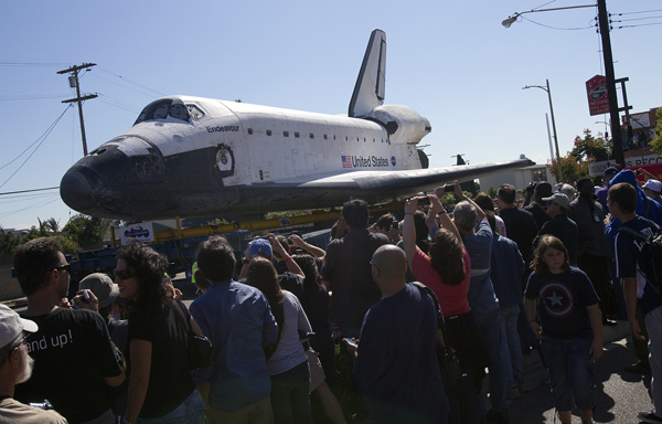 Endeavour towers over pedestrians as it passes by on La Tijera Blvd. in Los Angeles on Friday.