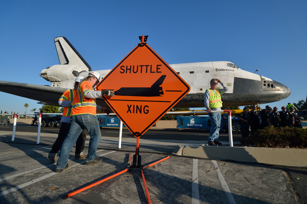 Work crews set up a sign as the Space Shuttle Endeavour makes its way to the Forum enroute to the California Science Center on Saturday.