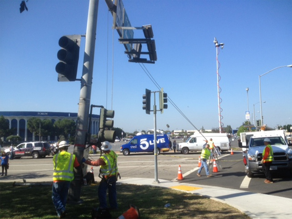 Workers erect a light post at Manchester Boulevard and Kareem Court.