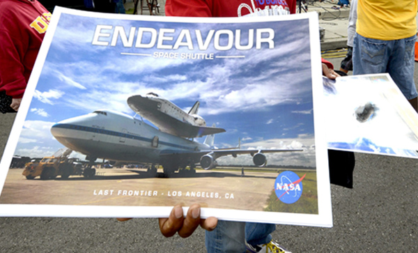 Man selling space shuttle Endeavour posters.
