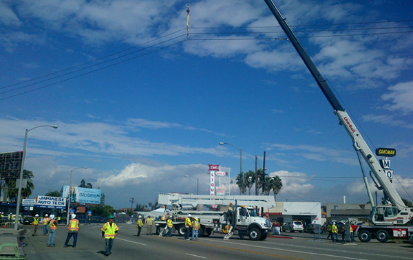 Southern California Edison employees lift electrical lines in Endeavour's path along Manchester Boulevard.