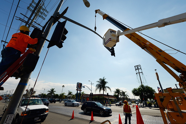 Workers prepare to bring down a street light temporarily to make room for the space shuttle Endeavour.