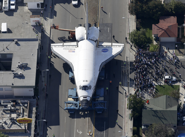 Spectators gather to watch the space shuttle Endeavour make its way down Manchester Blvd. on Friday.