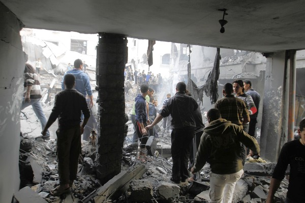Palestinians stand in the rubble of the Dalu family home after an Israeli airstrike in Gaza City.