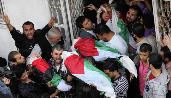 In Gaza City, Palestinians carry the bodies of members of the Dalu family killed in an Israeli airstrike.