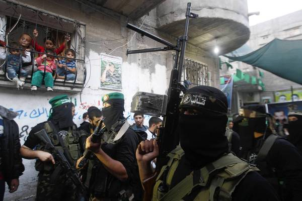 Children watch from a window grate as Hamas militants attend a news conference in Gaza City.