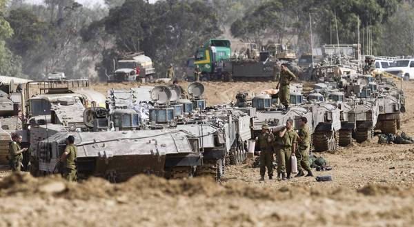 Israeli troops gather near the border with the Gaza Strip. The country is gearing up for a possible ground invasion of the Palestinian territory.