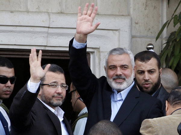 Hamas Prime Minister Ismail Haniyeh, second from the right, and Egyptian Prime Minister Hesham Kandil, left, wave to the crowd as they meet in Gaza City.