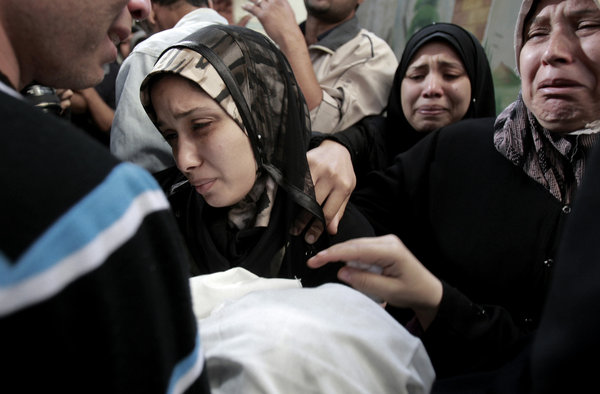 The parents of 11-month-old Omar Masharawi, killed in an Israeli airstrike, hold his body during his funeral in Gaza City on Thursday.