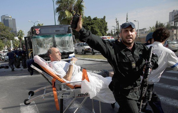 A wounded man is removed from the site of a bus bombing in Tel Aviv.