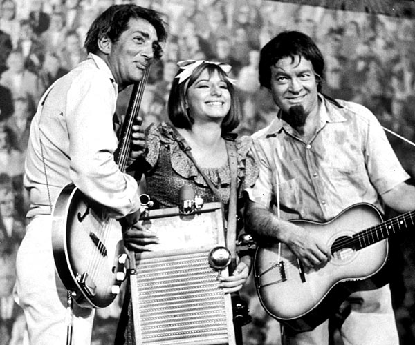Dean Martin, left, and Bob Hope play the guitar as Barbra Streisand plays a washboard and sings in a still from a television special in 1964.