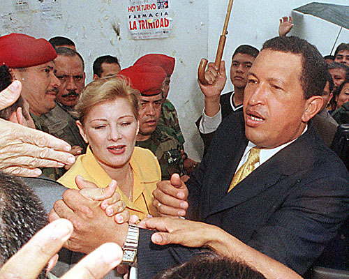 President Hugo Chavez with his wife Marisabel Chavez, shakes hands with supporters after voting on a proposed constitution.