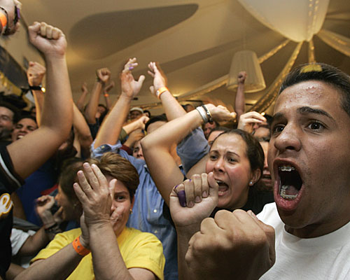 Members of Venezuela's opposition celebrate at their headquarters in the capital after hearing that President Hugo Chavez suffered a defeat in a vote on constitutional changes that would have let him run for reelection indefinitely.