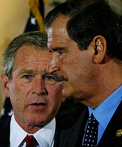 President George Bush talks with Mexican President Vicente Fox following their joint press conference during the Summit of the Americas in Monterrey, Mexico, on Jan. 12, 2004.